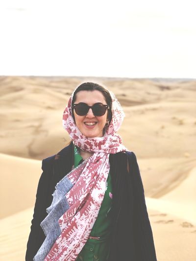 Portrait of smiling young woman in headscarf standing at desert