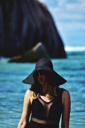 Woman wearing hat standing in sea