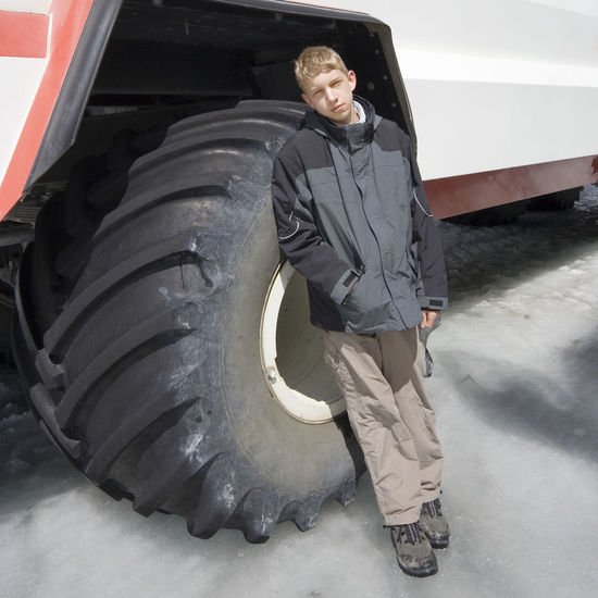 teenage boy in front of a large tire - columbia icefield, jasper national park, canada 4x4 All-terrain Boredom Boy Canada Full Length Ice Land Vehicle Large Leaning Offroad One Boy Only Outdoors Profile Public Transportation Scale  Snowmobile Standing Standing Teenage Boy Teenager Tire Transportation Transportation Vehicle