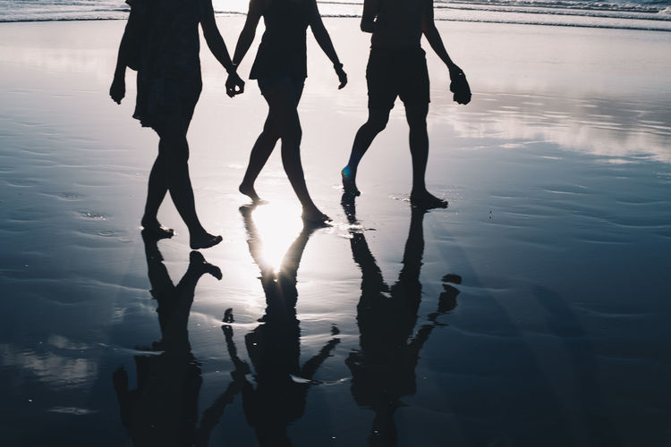 Low section of silhouette people walking on water