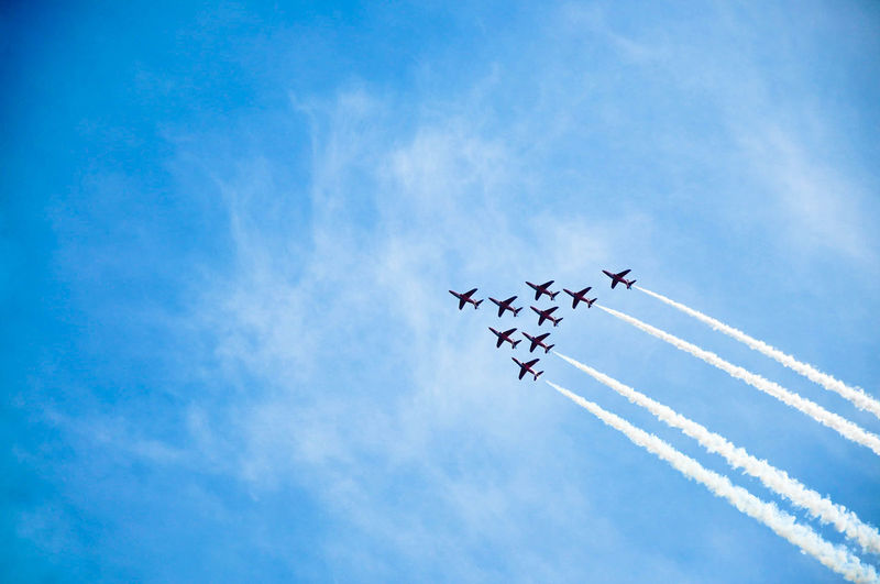 Low angle view of airplanes against blue sky