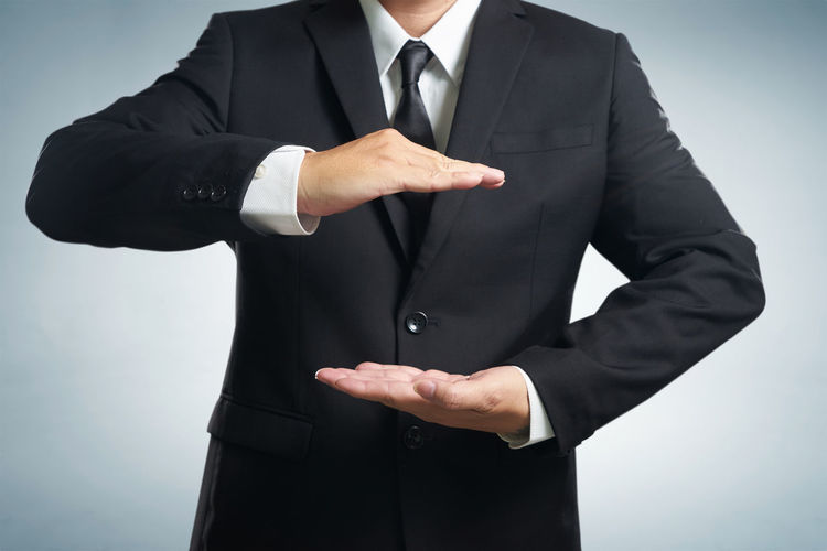 Midsection of businessman gesturing against gray background