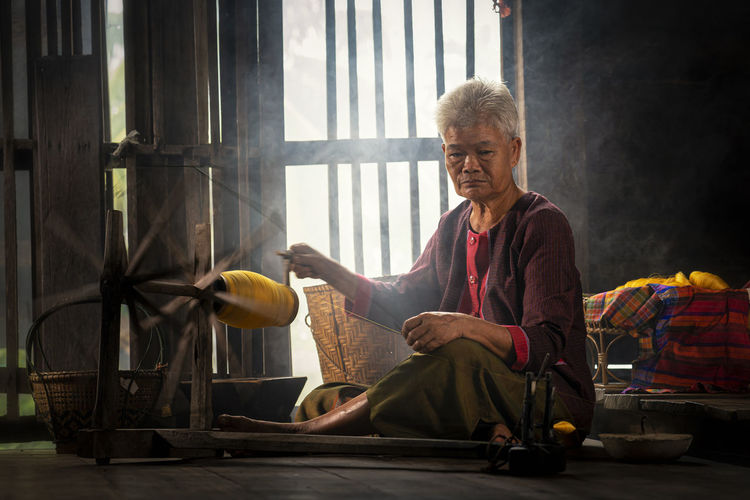 Portrait of mature woman with loom at home