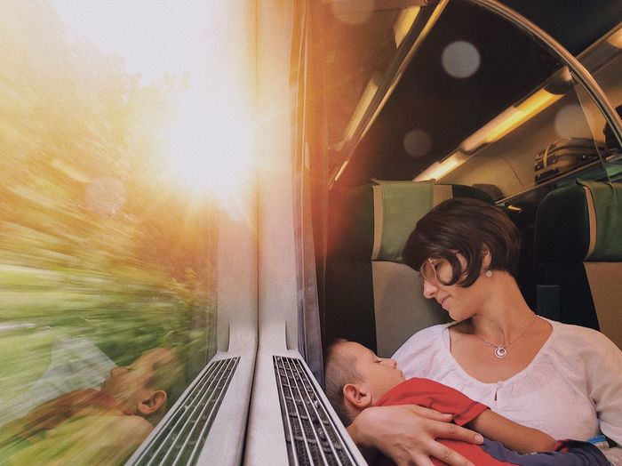 Close-Up Of Woman Carrying Son Sitting In Train