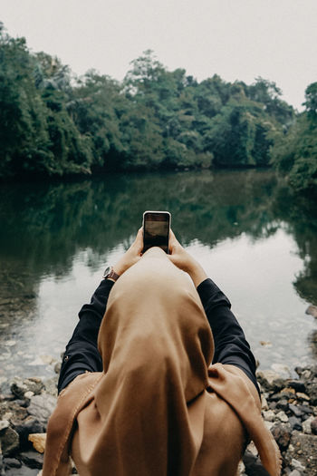 Rear view of woman photographing with smart phone by lake against trees and sky