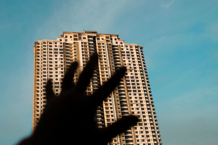 Low angle view of hand against building against sky