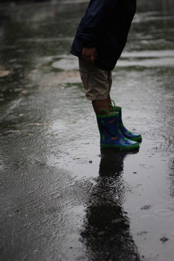 Low section of boy standing on puddle