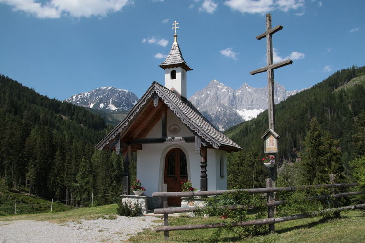 Traditional building by mountains against sky
