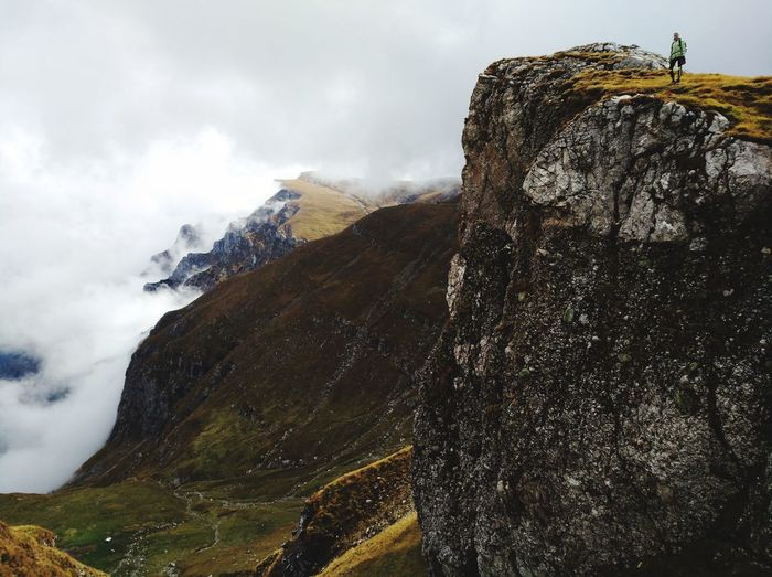 Low angle view of young woman standing on mountain against cloudy sky