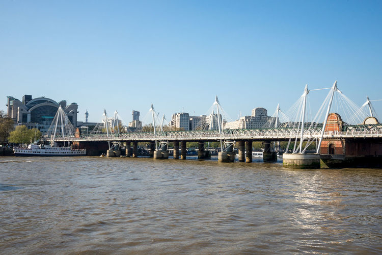 A view of Golden Jubilee and Hungerford bridges from South Bank of Thames River in London, England Golden Great Britain London Place South Thames River Tourist Attraction  United Kingdom View Architecture Bank Blue Sky Boat Bridge Capital City Cruise Hungerford Jubilee Pedestrian Ship Tourism Travel Destinations Visit