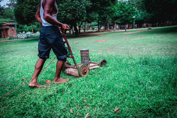 Low section of man cutting grass on field using lawn mower