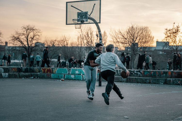 Sport Basketball - Sport Basketball Hoop Full Length Men Real People Leisure Activity Architecture Basketball - Ball Casual Clothing Togetherness Sky Lifestyles Court People City Motion Group Of People Building Exterior Tree Skill  Outdoors