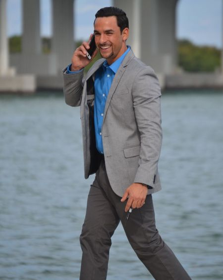 Smiling man in suit using mobile phone against lake