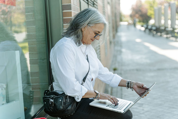 Midsection of woman using mobile phone while sitting on paper