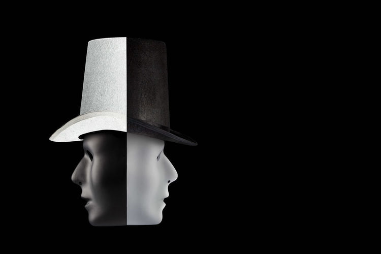 Black and white masks wearing top hat looking in opposite directions isolated on black background with copy space. Double talk and hypocrisy concept Actor Copy Space Two Faces Art Artificial Intelligence Black Black And White Black Background Close-up Concept Conceptual Copy Space Day Face Human Representation Hypocricy Hypocrisy Identity Mannequin Mask Model - Object No People Paper Single Object Studio Shot Top Hat White White Mask