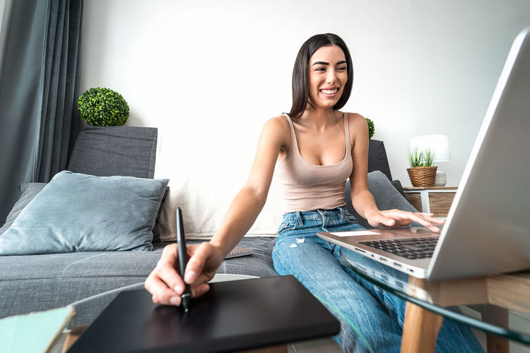 Smiling young woman using laptop and graphics tablet at home