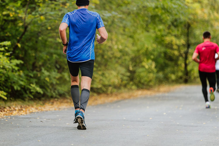 Rear view of man jogging on road