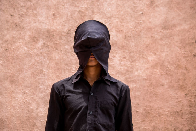 Teenage boy covering face with mask while standing against wall