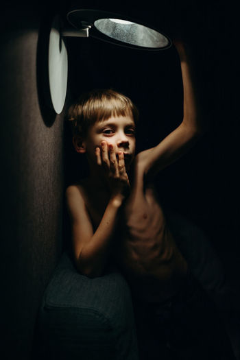 Portrait of boy standing under illuminated light at home