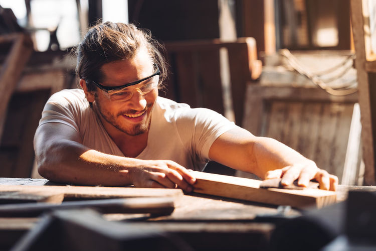 A young male carpenter builder working overall equals a wooden bar with a milling machine