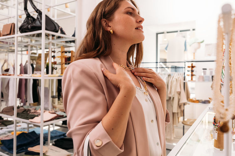 Side view of young woman looking away at store