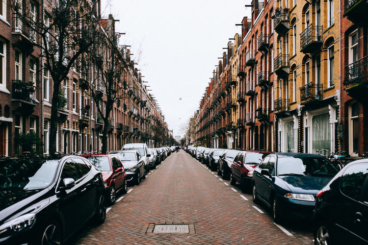 Cars Parked On Street Amidst Buildings Against Sky