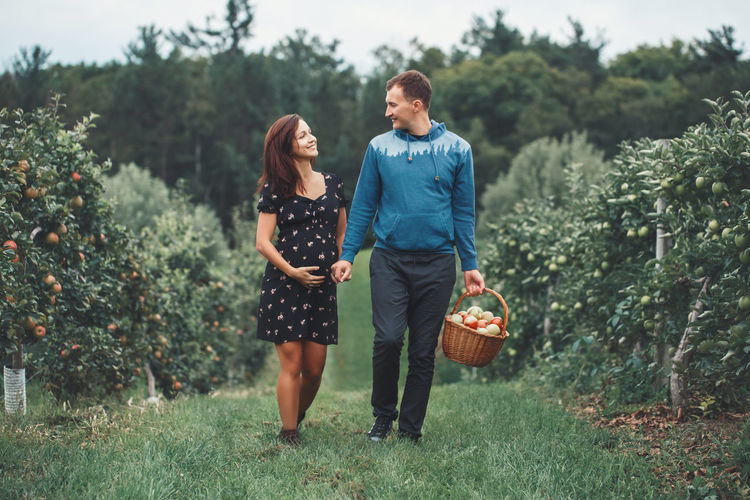 Man walking with pregnant woman at farm