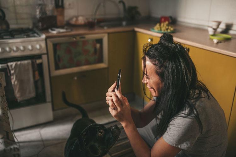 Woman holding camera at home