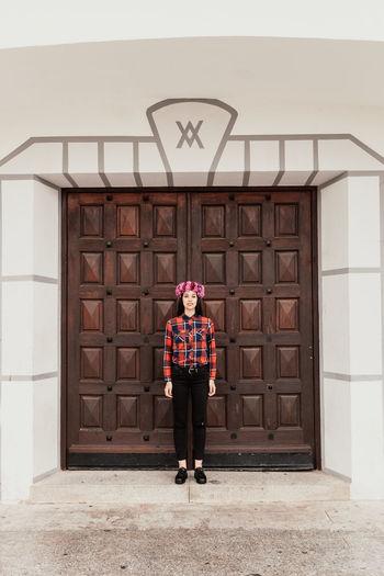 Portrait of man standing against door of building