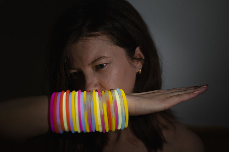 Close-up portrait of girl with neon bracelets