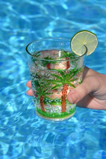 Cropped image of hand holding drink at swimming pool