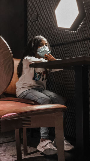 Low angle view of girl wearing mask sitting in cafe