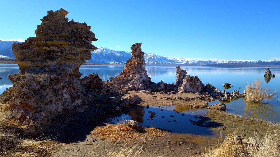 Rock formations in lake against clear blue sky