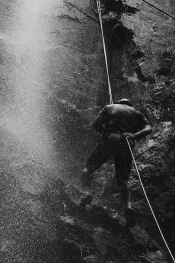Rear view of man climbing on mountain by waterfall