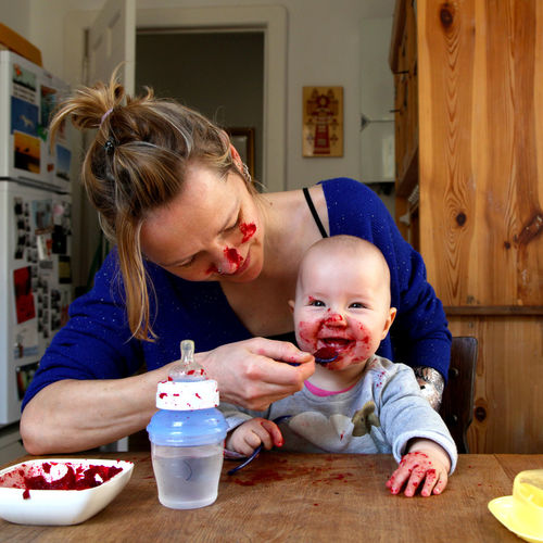 Woman feeding baby at kitchen table