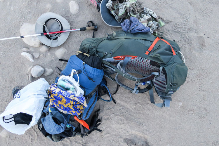 Hikers bags open on sandy ground Adventure Backpack Bag Clothes Couple Day Directly Above Equipment Explore Hat High Angle View Hike Hiker Hiking His And Hers Luggage No People Outdoors Pole Sand Scarf Travel Walk Let's Go. Together.