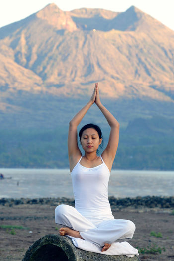 Woman doing yoga against mountains