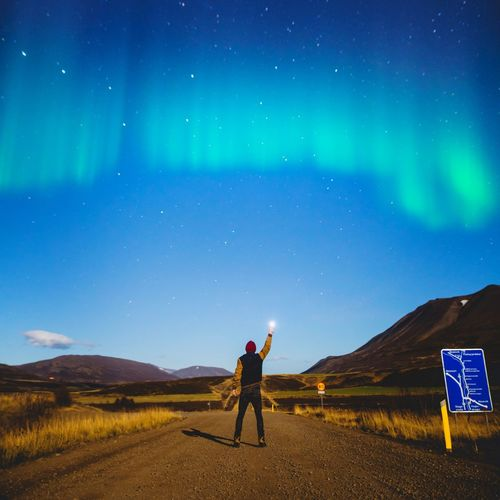 Full length of man with arms raised against sky at night