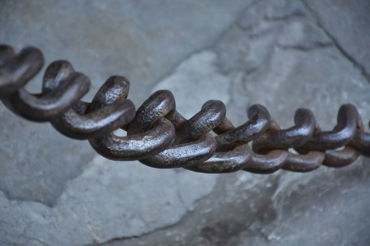 Close-up of metallic chain by wall
