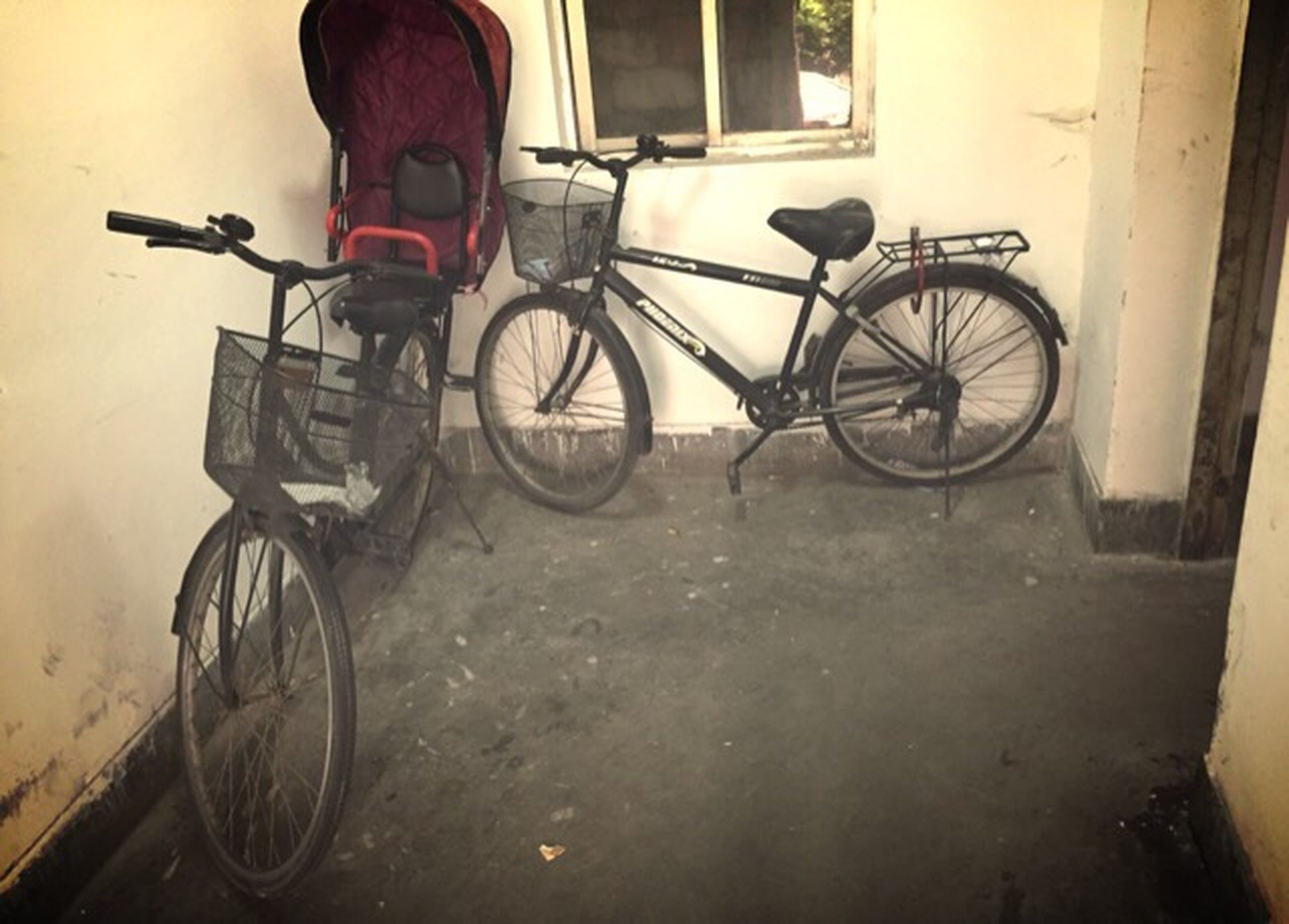 bicycle, mode of transport, stationary, transportation, land vehicle, parking, parked, built structure, architecture, wall - building feature, building exterior, wheel, house, day, door, window, street, leaning, wall, no people