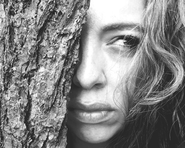 Close-up of young woman looking away by tree trunk