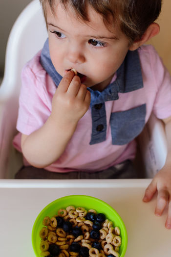 High Angle View Of Baby Boy Eating Breakfast Cereal At High Chair