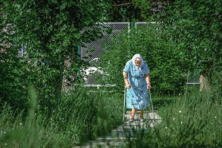 Senior Woman Walking On Steps With Canes Amidst Plants
