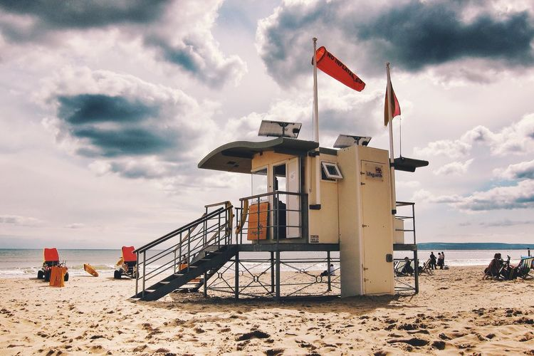 Lifeguard hut on beach against cloudy sky