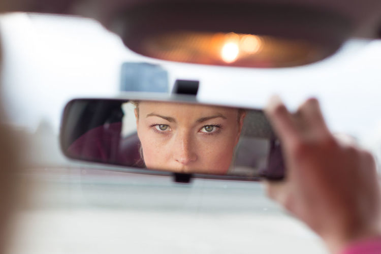Portrait of woman reflecting in car