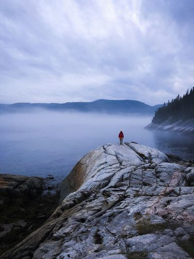 Rear view of woman standing on cliff with lake in background against cloudy sky