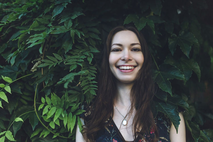 Portrait of cheerful optimistic brunette in a green foliage, smiling. close up.