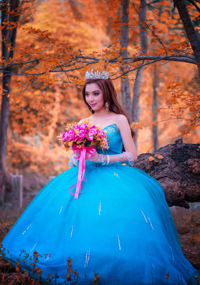 Beautiful Asian woman flower bouquet on hand with traditional dress, Thai girl wearing princess dress in her hand holding a flower. Adult Autumn Beautiful Woman Beauty In Nature Change Day Fashion Fashion Model Forest Full Length Leaf Leisure Activity Lifestyles Nature One Person One Young Woman Only Outdoors People Portrait Real People Smiling Standing Tree Young Adult Young Women