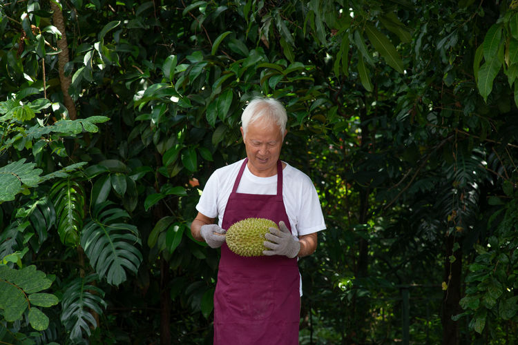 Man holding durian while standing against plants