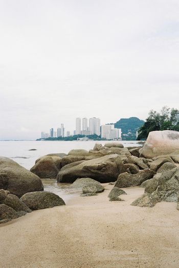 Captured on analog film, Shamrock Beach Villas is a peaceful spot in busy Penang Island, Malaysia. Camera: Leica Minilux Film: Kodak Pro Image 100 Batu Ferringhi Ishootfilm Leicaminilux Penang Beach Beauty In Nature Buyfilmnotmegapixels Day Malaysia Nature No People Outdoors Pro Image 100 Sand Sea Shamrock Beach, Shootfilmstaybroke Sky Skyscraper Staybrokeshootfilm Staypoorshootfilm Urban Skyline Water